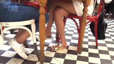 Sexy crossed legs feets miniskirt under table